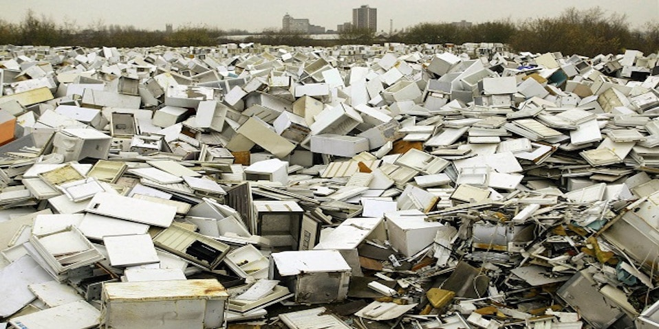 Disused fridges and freezers lie piled up in a storage yard in Manchester.